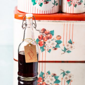 Bottle of cherry brandy in front of a vintage tin.