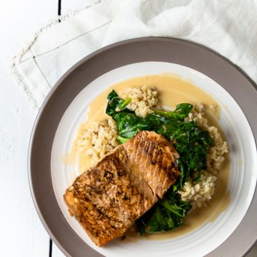 Plate of salmon on spinach on brown rice