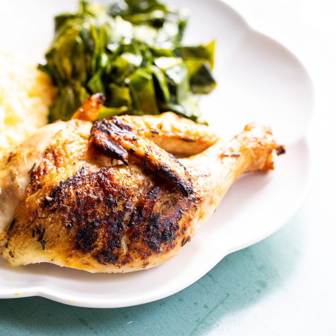Grilled chicken leg on a white plate.