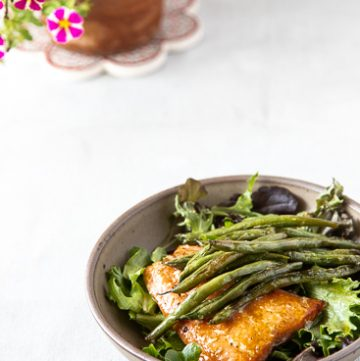 Salmon and green beans on a bowl of salad greens.