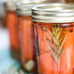 Jar of pickled carrots with a rosemary sprig.