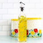Bottle of lemon herb vinegar - bright yellow in a pretty painted bottle.