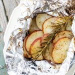 Close up of sliced potatoes and rosemary in a foil packet