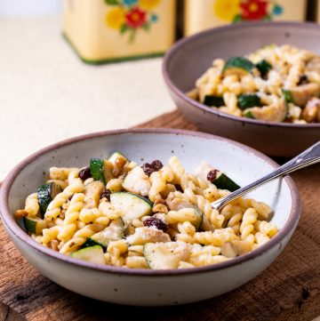 Two bowls of pasta with zucchini.