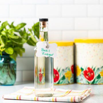 Bottle filled with liquid labeled Basil Vinegar.