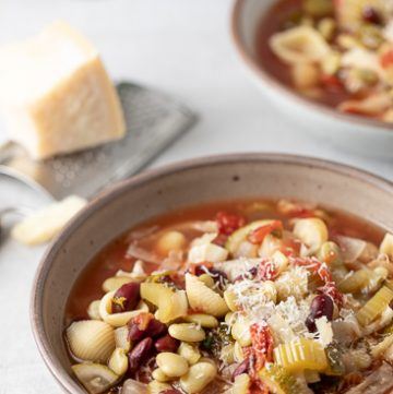 Bowl of minestrone soup garnished with Parmesan Cheese.