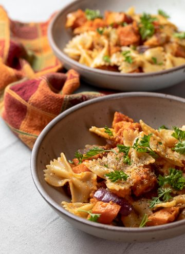 Two Bowls of pasta with sweet potatoes and bacon.
