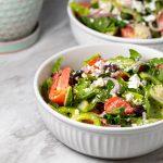 Greek salad in a white bowl.