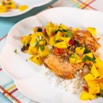 Plate of salmon topped with mango salsa.