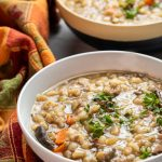 Two bowls of beef barley and mushroom soup.