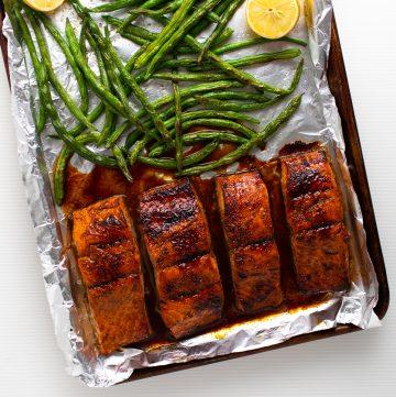 Glazed salmon on a foil lined baking sheet.