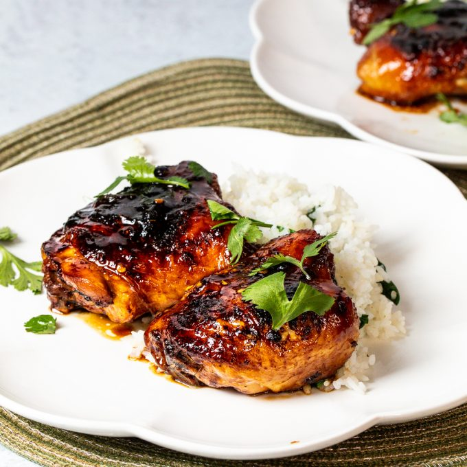 Two sticky Thai Chicken thighs on a plate.