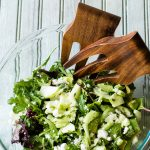 Bowl with Green Salad and wooden salad tossers.