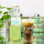 Mint Lemon Simple Syrup in a bottle next to a glass of iced tea.