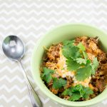 Bowl of chili topped with cheese and cilantro