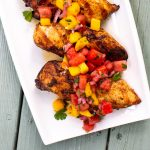 Plate of grilled chicken topped with a mango watermelon salsa.