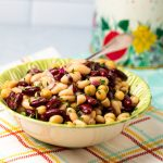 Green bowl filled with a 3 bean salad.