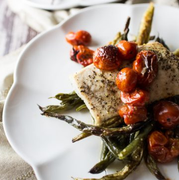 Mahi Mahi on a white plate with green beans and tomatoes.