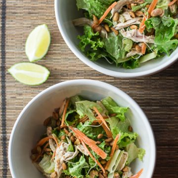 Two white bowls with chicken salad.