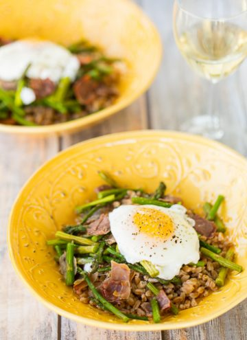 Farro Grain bowl topped with roasted asparagus, proscuitto, and an egg.