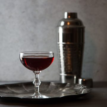 Deep red cocktail on a silver plate with a cocktail shaker.
