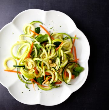Zoodle salad on a scalloped plate.