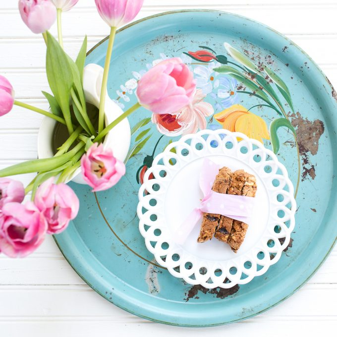 Blue tray with a plate of biscotti and vase of tulips.