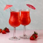 Two glasses filled with deep red frozen cocktails.