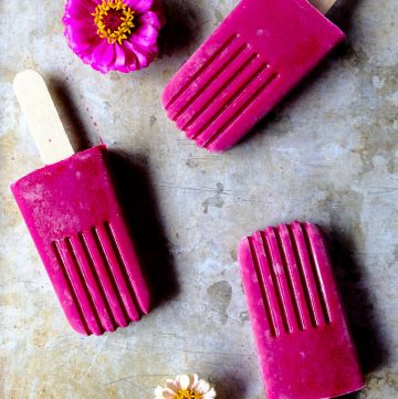 Three Bright pink popsicles with flowers on a tray.