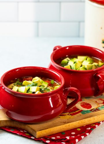 Two red bowls of soup topped wit avocado.