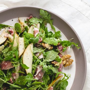 Plate with salad with arugula, pears, and walnuts.