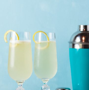 Two flute glasses with yellow cocktail and lemon twist with a blue cocktail shaker.