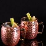 Two copper mugs with celery stick and lemon garnish.