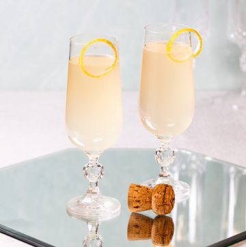 Two sparkling cocktails with a popped champagne cork.