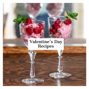 Two goblets filled with pink ice cream and topped with raspberries.