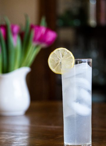 Tom Collins Cocktail in front of a vase of flowers