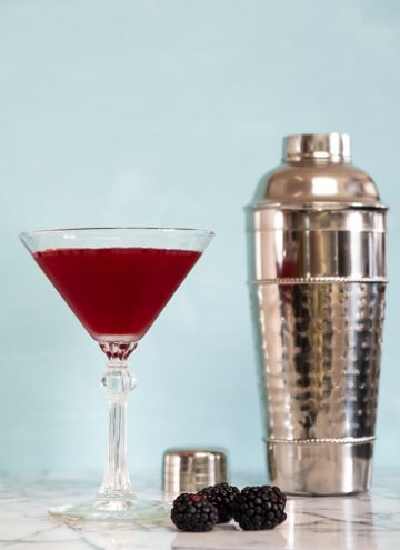 Blackberry martini in front of a cocktail shaker