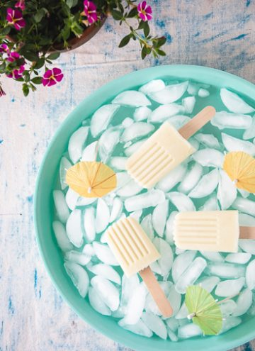 Piña Colada popsicles on a blue ice filled tray.