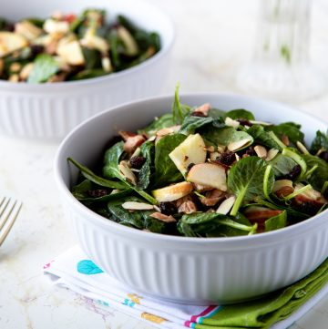 White bowl filled with spinach salad with apples.
