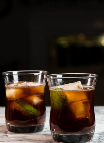 Two glasses filled with a Cuba Libre cocktail.