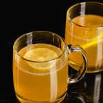 Two mugs filled with a hot toddy.