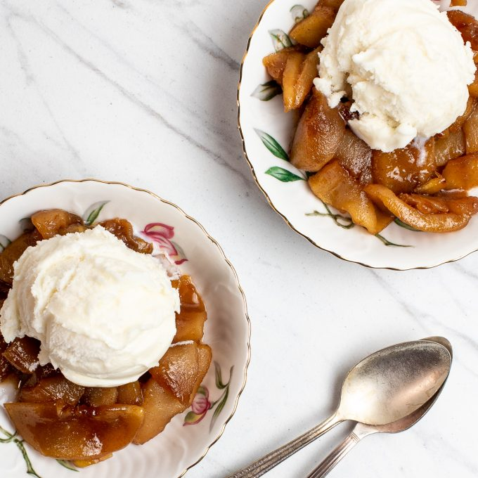 Two bowls of fried apples topped with ice cream.