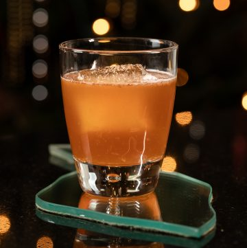 Orange cocktail with nutmeg grated on the top.