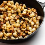 Golden brown potatoes in a cast iron skillet.