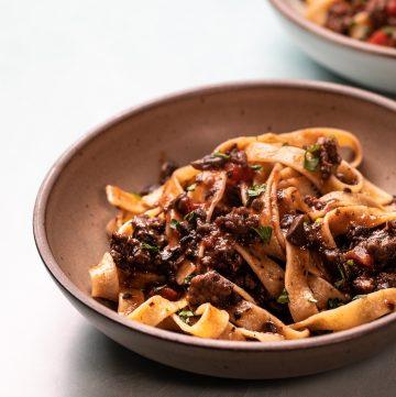 Bowl of pasta topped with mushroom and sausage ragu.