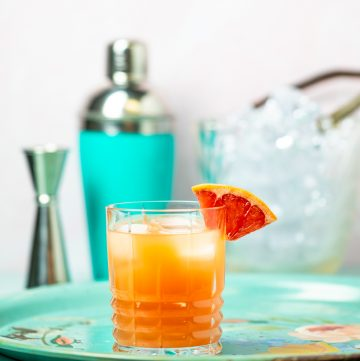 Orange cocktail garnished with a grapefruit wedge.