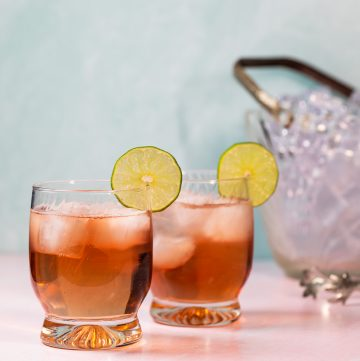 Two pink cocktails garnished with a lime wheel.