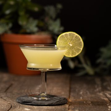 Yellow cocktail garnished with a lime wheel.