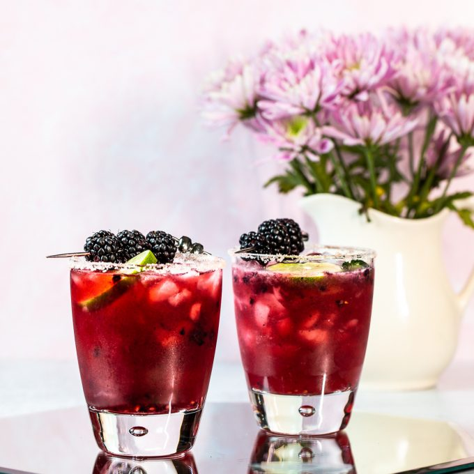 Two dark purple cocktails garnished with blackberries and rimmed with salt.