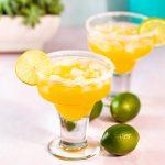 Bright orange mango margarita in a salt rimmed glass.